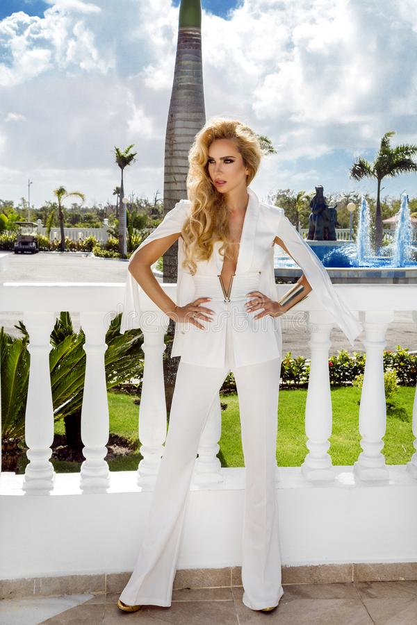 Beautiful sexy successful woman young blonde wear in stylish white jumpsuit and high heels clutch accessory style clothes for a royalty free stock image