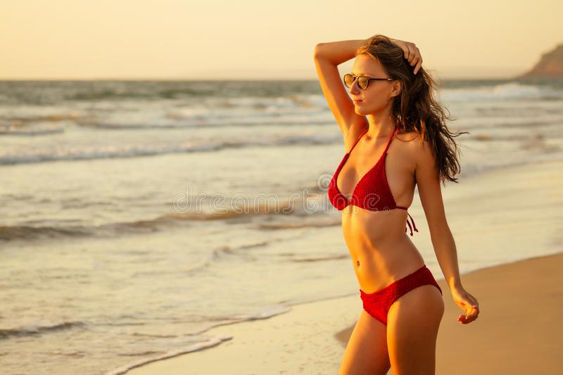 Beautiful sexy tanned model in red colour swimsuit on sand beach near ocean at sunset. Travel concept spf sunscreen sun. Protect stock images