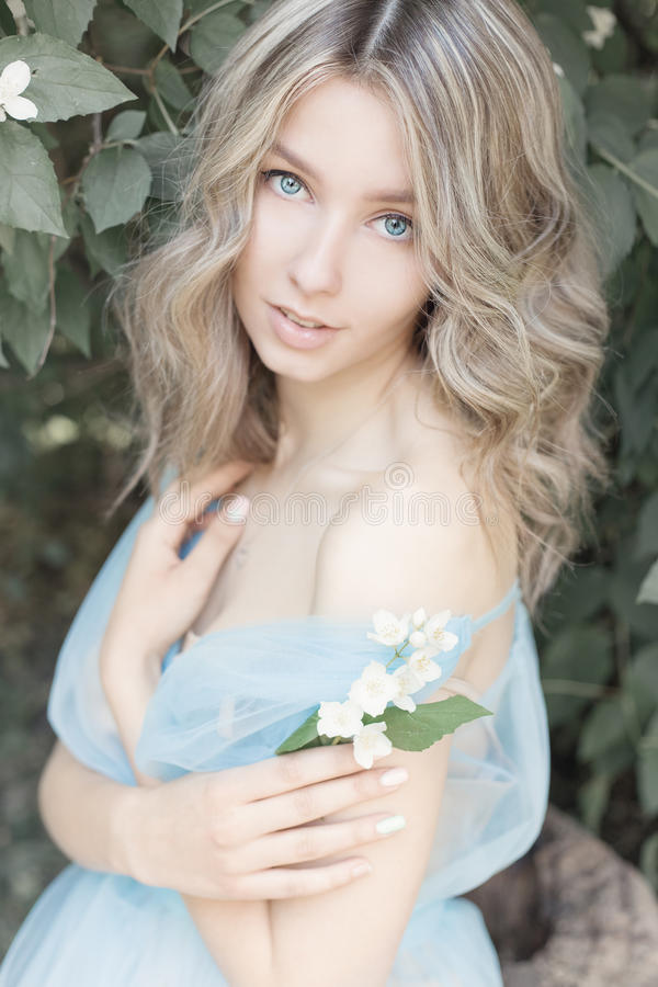 Beautiful tender blonde girl in blue light dress with a sprig of jasmine in his hands sitting the garden in the style. Beautiful blonde girl in blue light dress royalty free stock images