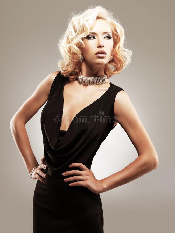 Beautiful white woman in black dress stock image