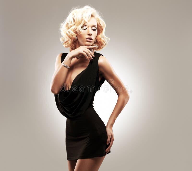Beautiful white woman in black dress. Posing at studio stock photography