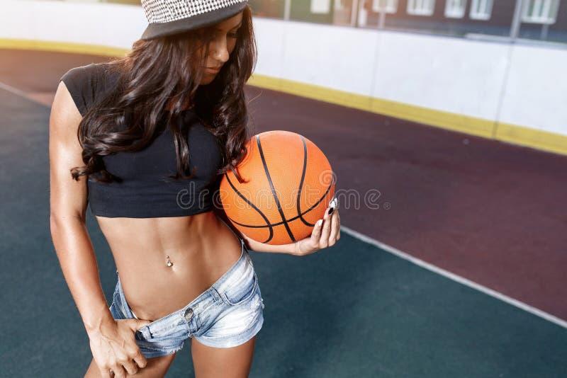 Beautiful woman basketball player posing outdoors on street. Beautiful brunette woman basketball player posing outdoors on street in jeans royalty free stock images