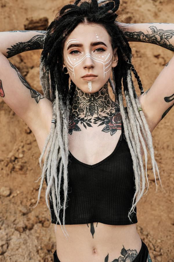Beautiful sexy woman in black underwear. The body is covered with many tattoos. Dreadlocks on the head . Posing against. Beautiful sexy woman in black underwear royalty free stock image