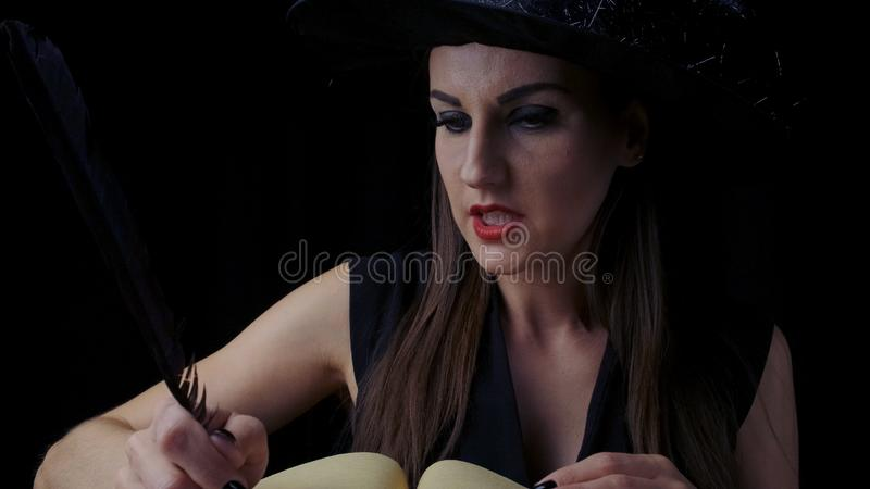 Beautiful sexy woman in a black witch costume and hat, conjures over a book with a pen, writes a pen in a book royalty free stock photo