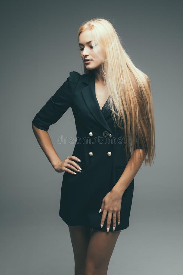 Beautiful woman blond hair wear dress back casual street style model designer grey background royalty free stock photo