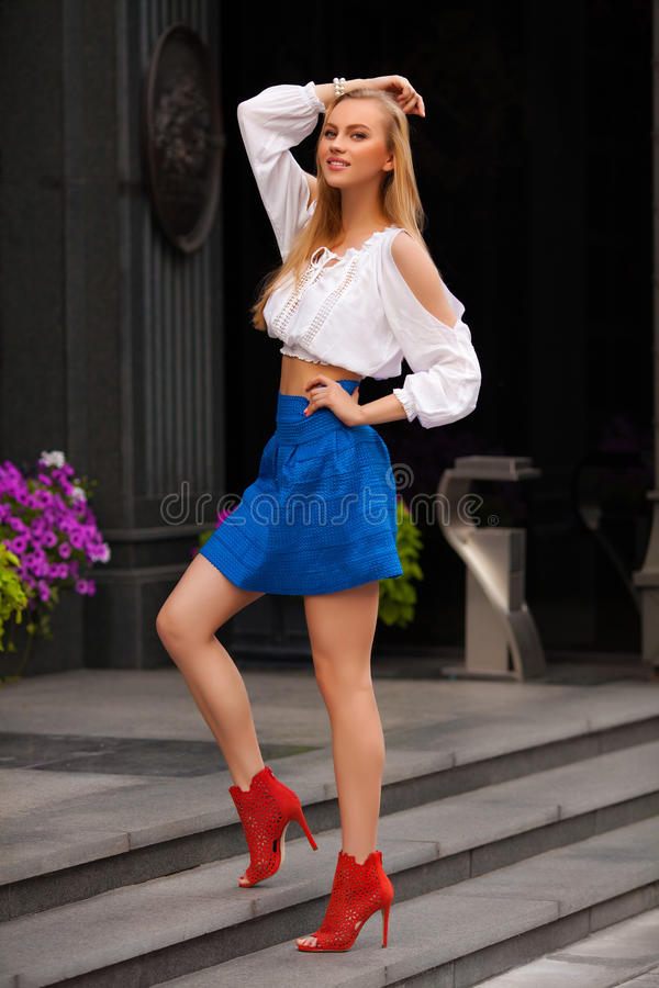 Beautiful woman with blue skirt and blond hair posing outdoor. Fashion girl stock image