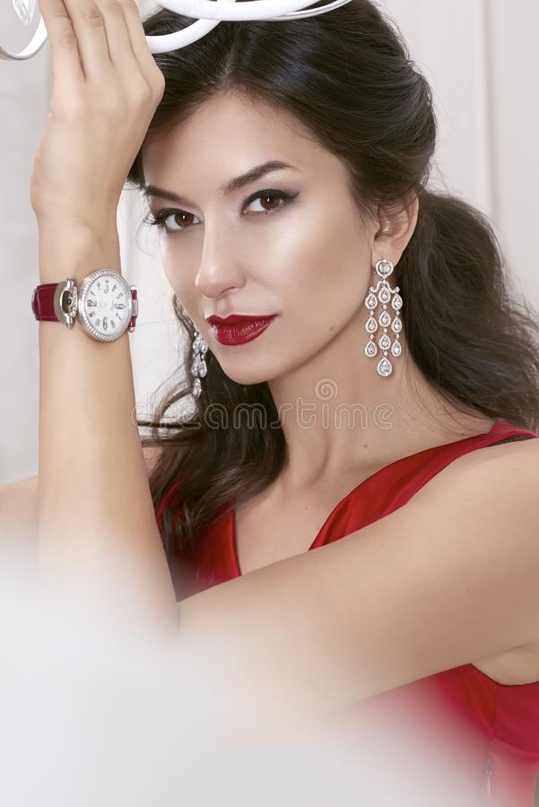 Beautiful woman brunette Brown eyes in a red dress in lavis. H earrings with diamonds and watches on the Burgundy leather strap evening makeup, red lipstick stock photo