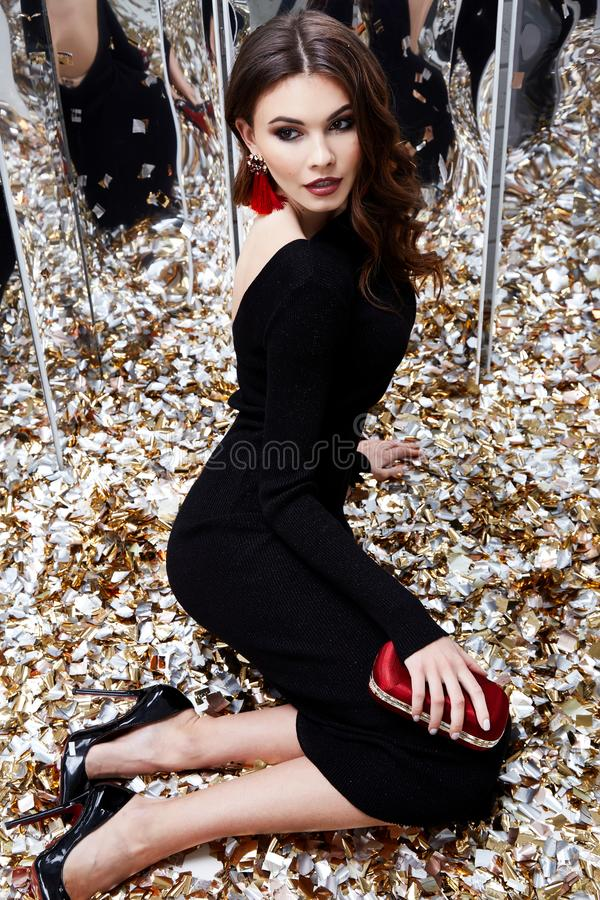Beautiful woman brunette hair evening makeup pretty face we. Ar luxury black dress skinny fit style celebrate party holiday Christmas New Year mirror shiny royalty free stock photography