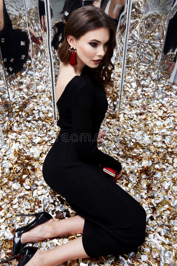 Beautiful woman brunette hair evening makeup pretty face we. Ar luxury black dress skinny fit style celebrate party holiday Christmas New Year mirror shiny stock image