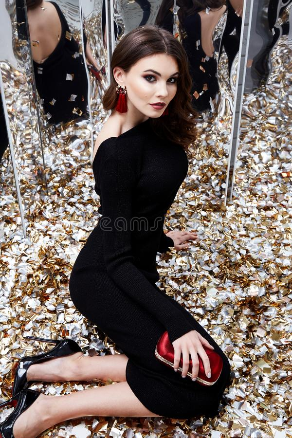 Beautiful woman brunette hair evening makeup pretty face we. Ar luxury black dress skinny fit style celebrate party holiday Christmas New Year mirror shiny royalty free stock images