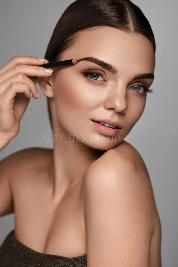 Beautiful Woman Contouring Eyebrows. Glamorous Makeup royalty free stock images