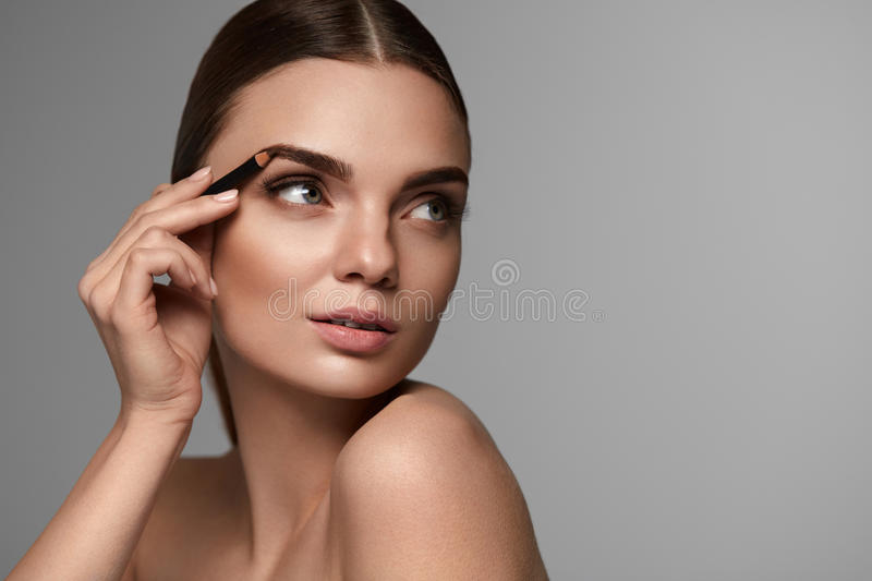 Beautiful Woman Contouring Eyebrows. Glamorous Makeup royalty free stock photography