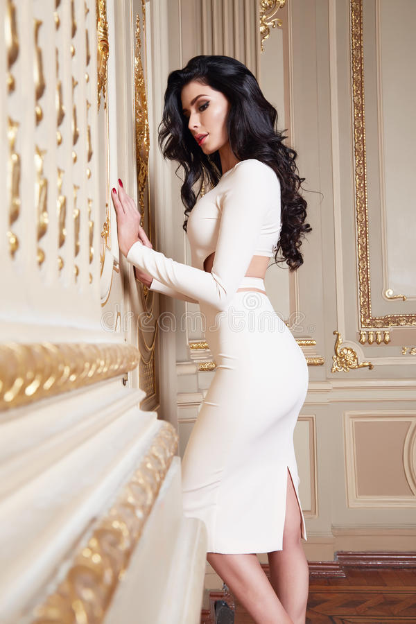 Beautiful woman in elegant dress fashionable autumn Collection of spring long brunette hair makeup tanned slim body figure ac. Cessories interior luxury castle royalty free stock photos