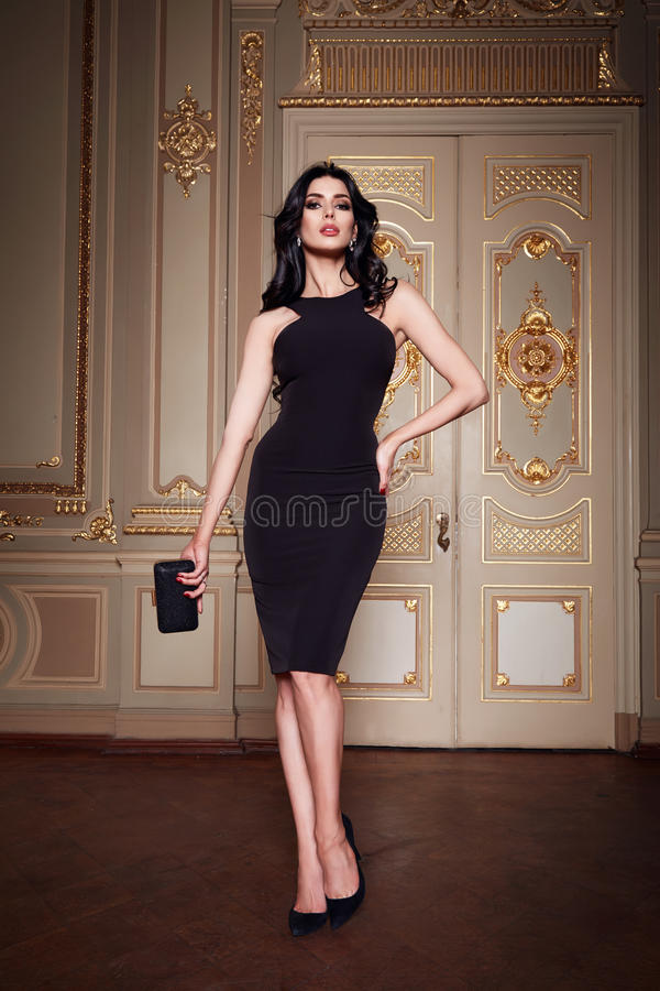 Beautiful woman in elegant dress fashionable autumn Collection of spring long brunette hair makeup tanned slim body figure ac. Cessories interior luxury castle royalty free stock images