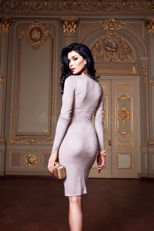Beautiful woman in elegant dress fashionable autumn Collection of spring long brunette hair makeup tanned slim body figure ac stock photography