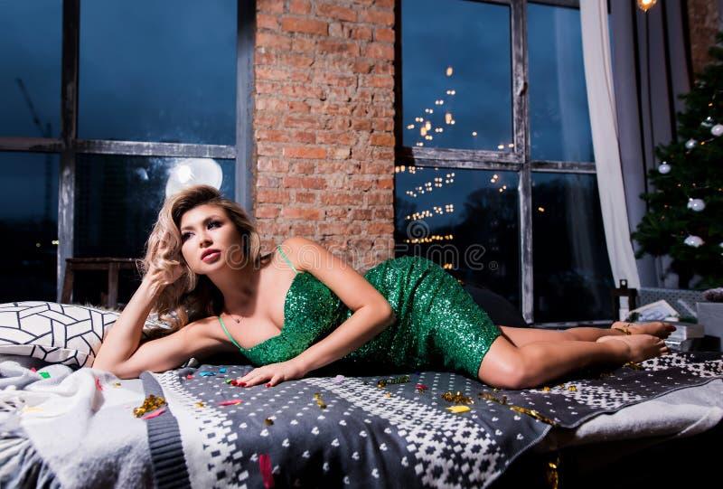 Beautiful woman in elegant green sparkling dress lying on modern sofa. Fashion model with long legs posing in dark interior. royalty free stock photos