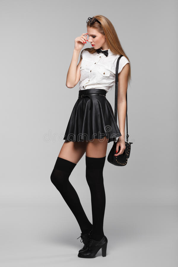 Beautiful woman is in fashion style in black mini skirt. Fashion girl stock photography