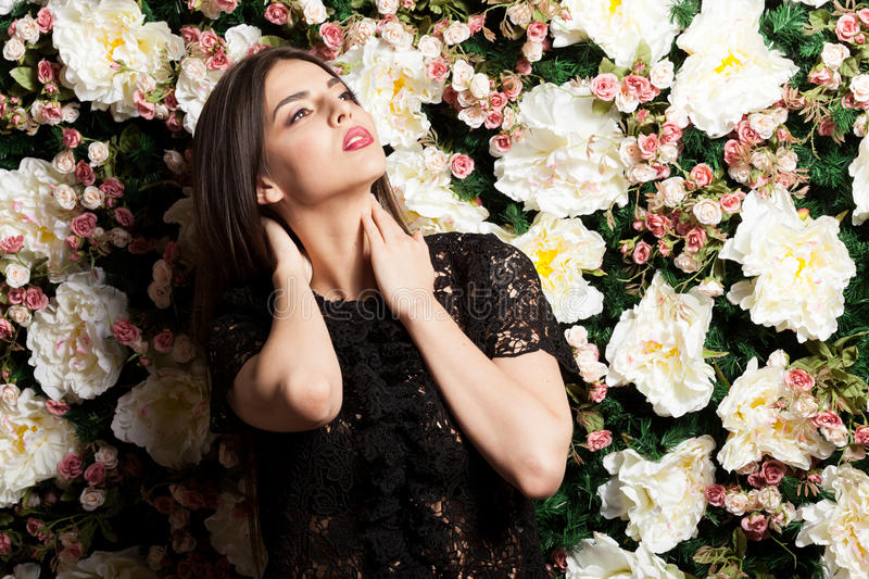 Beautiful woman on flower wallpaper background in studio ph royalty free stock photos
