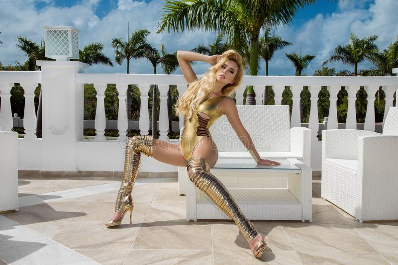Beautiful sexy woman in gold bikini and gold shoes posing on the caribbean luxury hotel stock photo