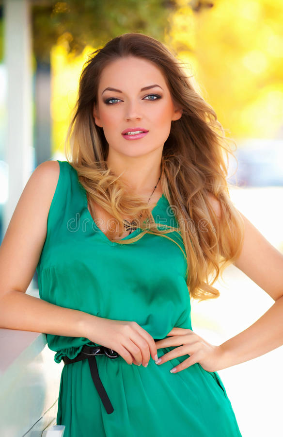Beautiful woman with green dress and blond hair outdoor. Fashion girl stock image