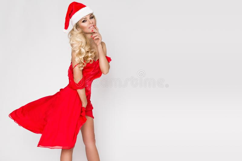 Beautiful woman model with long disheveled blond hair stand. Ing on a white background dressed in a red silk dress and cap Santa Claus and joyfully smiles in stock images