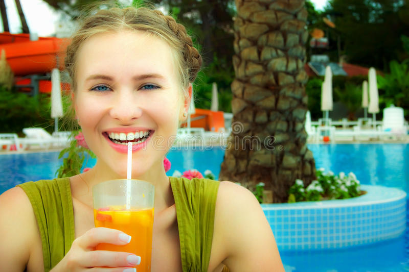 Beautiful woman near pool drinking cocktail royalty free stock photography