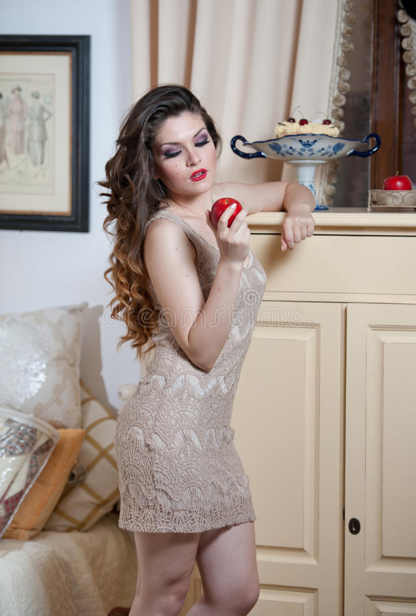 Beautiful woman in nude colored lace dress in vintage scenery holding a red apple in her hand. Long curly hair brunette. Young woman with makeup in luxury royalty free stock photos