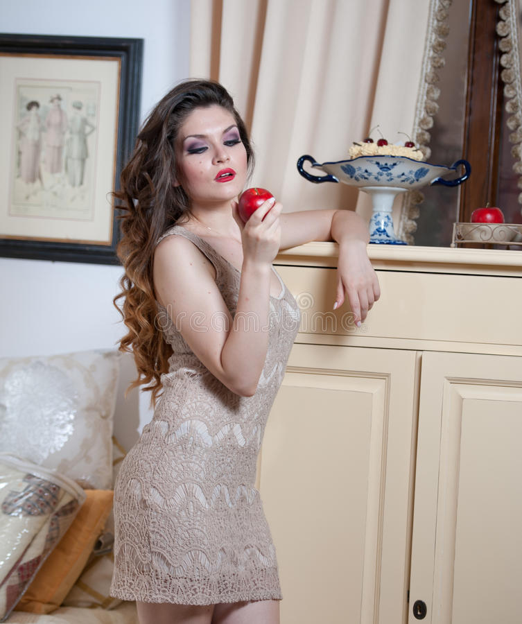Beautiful woman in nude colored lace dress in vintage scenery holding a red apple in her hand. Long curly hair brunette. Young woman with makeup in luxury stock photo