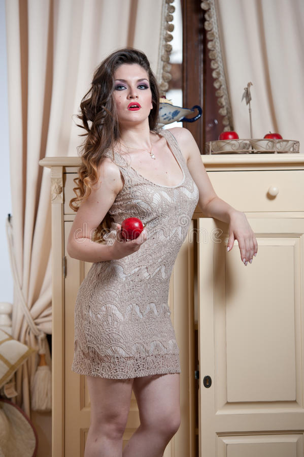 Beautiful woman in nude colored lace dress in vintage scenery holding a red apple. Long curly hair brunette young women stock photos