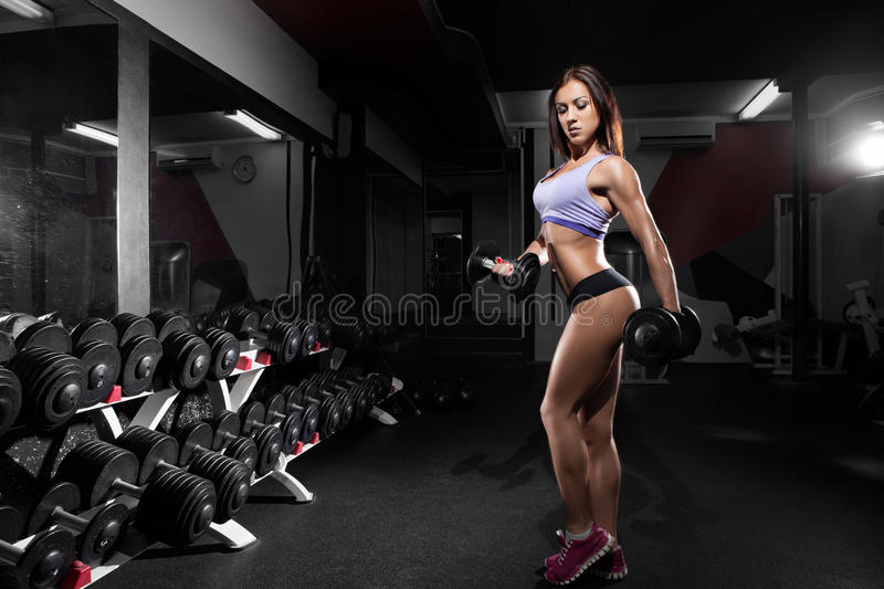 Beautiful woman with perfect abdominal muscles at the gym royalty free stock photography