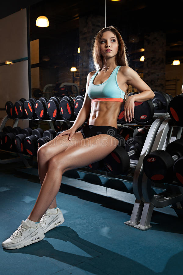 Beautiful woman with perfect abdominal muscles at the gym royalty free stock image