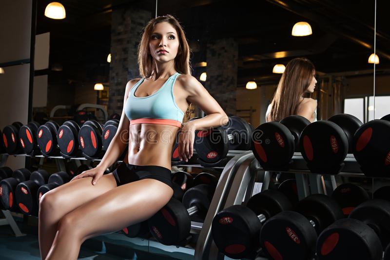 Beautiful woman with perfect abdominal muscles at the gym stock photos