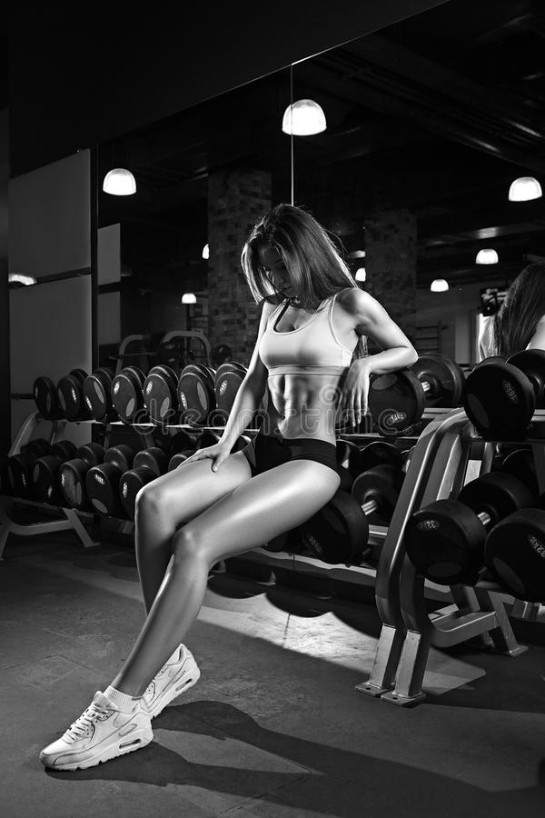 Beautiful woman with perfect abdominal muscles at the gym stock image