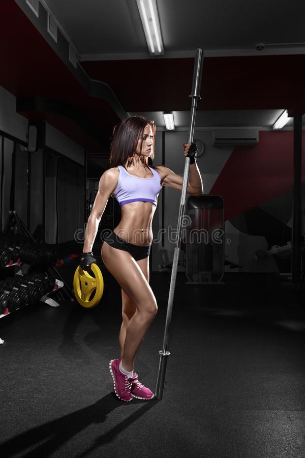 Beautiful woman with perfect abdominal muscles at the gym stock photography