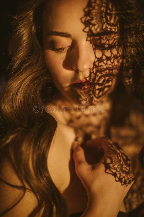 Beautiful sexy woman portrait with lace shadows. Hot summer night passion. Attractive female Slavic appearance. Long royalty free stock photography