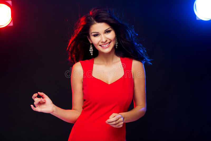 Beautiful woman in red dancing at nightclub stock images