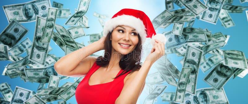 Beautiful woman in santa hat over money rain royalty free stock photo
