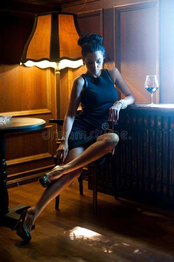 Beautiful woman in short tight black dress sitting on chair and relaxing with a wine glass near her. Woman with long legs. Posing challenging in dark vintage royalty free stock photography