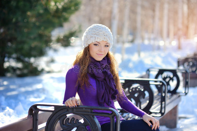 Beautiful and woman sitting on bench in winter.  royalty free stock image