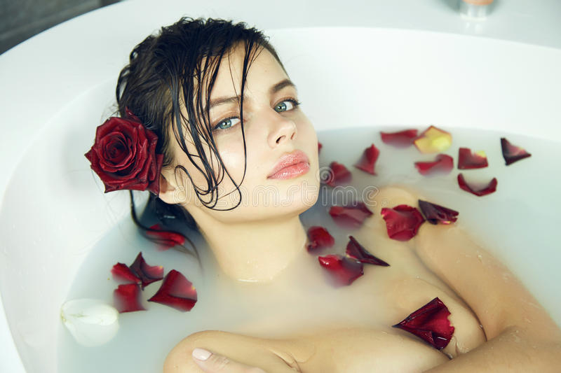 Beautiful woman takes bath rose candles Valentine's day spa royalty free stock images
