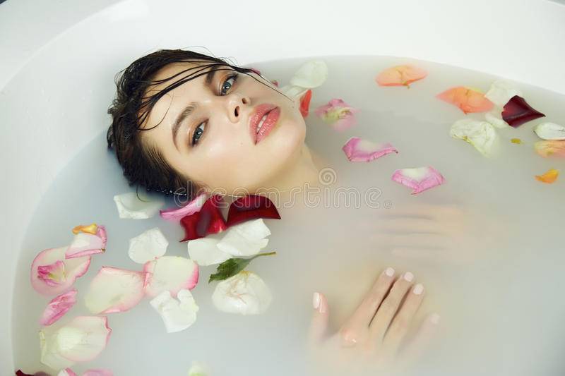 Beautiful woman takes bath rose candles Valentine's day spa stock images