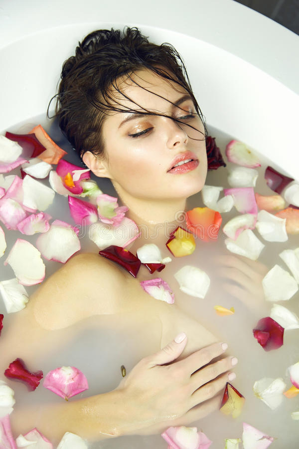 Beautiful woman takes bath rose candles Valentine's day spa stock photography