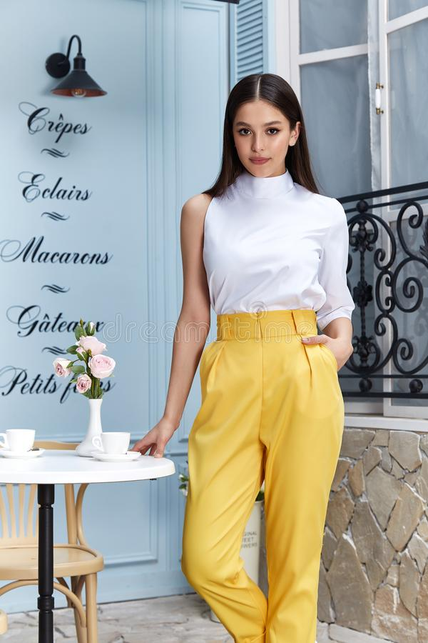 Beautiful sexy woman wear fashion summer collection clothes casual style blouse yellow trousers slim body pretty face model. Accessory jewelry brunette hair royalty free stock images