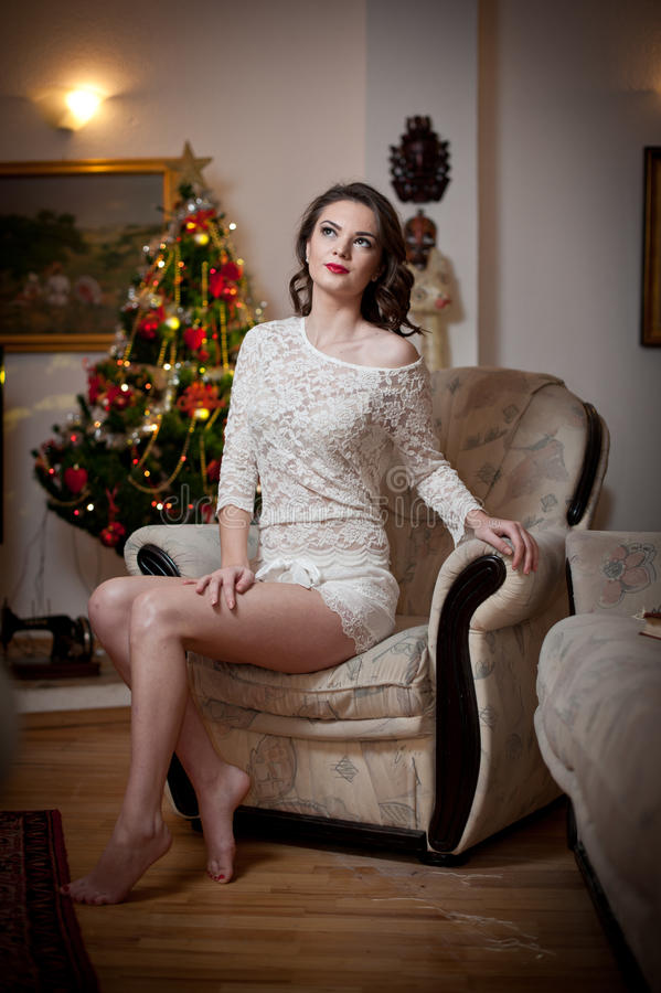 Beautiful Woman With Xmas Tree In Background Sitting On