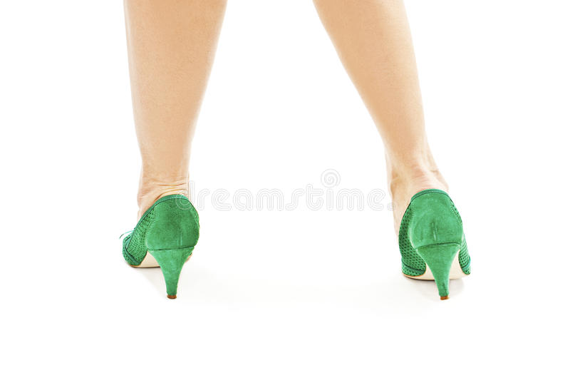 Beautiful, sexy, women's legs in green shoes from the back royalty free stock image