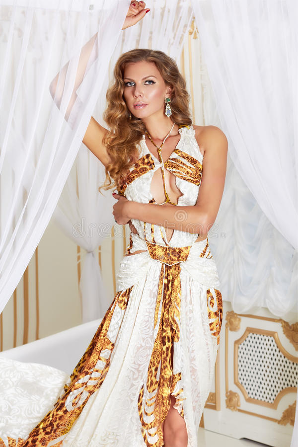 Beautiful young blonde woman with long curly hair and make-up wearing a long evening dress white with gold embroidery and stock photo