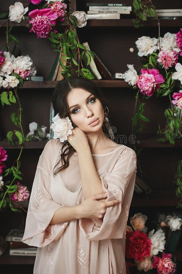 Beautiful and young brunette model woman, in grey dress, is posing with flowers in library stock image