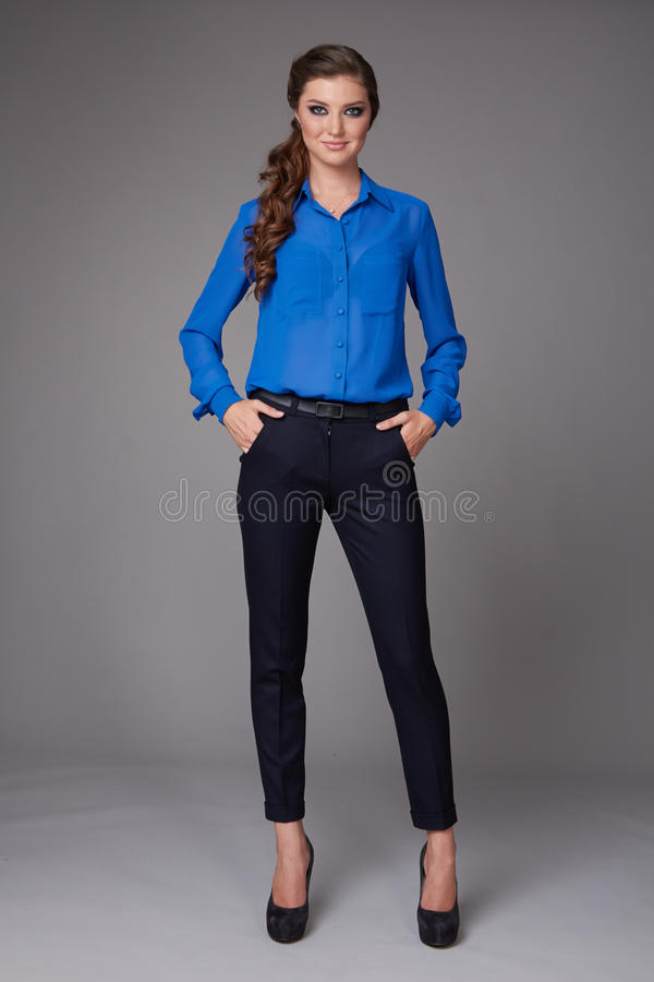 Beautiful young business woman with evening make-up dressed in tight pants and silk blouse with lace long sleeves and high-he stock photo
