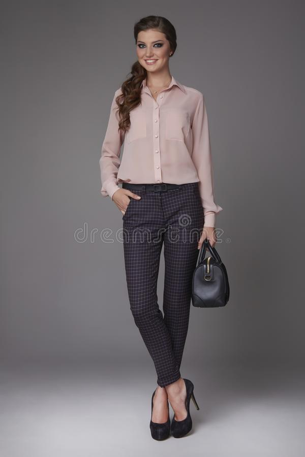 Beautiful young business woman with evening make-up dressed in tight pants and silk blouse with lace long sleeves and high-he. Eled shoes small black handbag royalty free stock photos