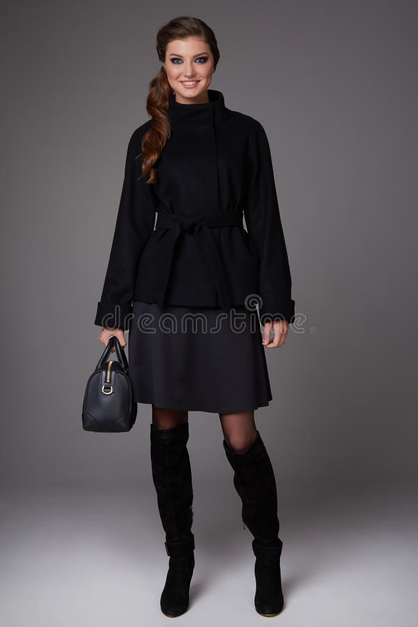 Beautiful young business woman with evening make-up wearing a dark skirt to the knee wool red coat jacket high boots high hee. Ls, business clothes for meetings stock photography